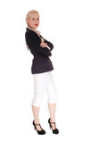 Business woman standing in jacked and white pants. A beautiful tall blond business woman standing in a black jacked and Royalty Free Stock Photography