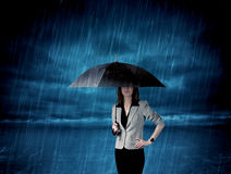 Business woman standing in rain with an umbrella Stock Images