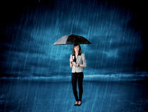 Business woman standing in rain with an umbrella Royalty Free Stock Photography