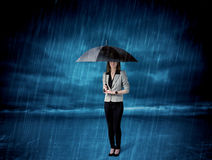 Business woman standing in rain with an umbrella Royalty Free Stock Photos