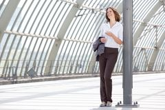 Business woman standing at station with mobile phone Royalty Free Stock Photography