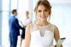Business woman standing straight and smilling in office Royalty Free Stock Images