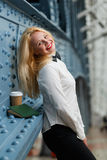 Business woman standing at wall with note book and coffee Stock Photos