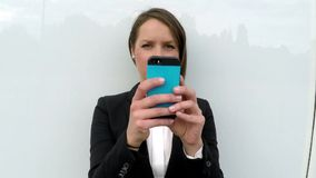 Business woman standing by the white glass wall with smart phone stock video