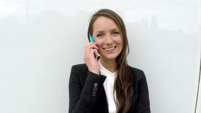 Business woman standing by the white glass wall with smart phone stock video footage