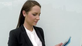 Business woman standing by the white glass wall with tablet stock video