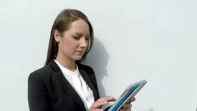 Business woman standing by the white glass wall with tablet stock footage