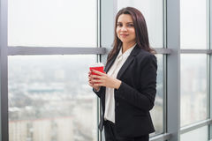 Business woman standing at  window with cup Royalty Free Stock Photography