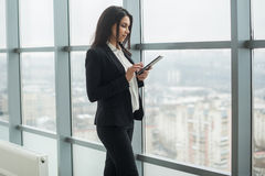 Business woman standing at window with tablet Royalty Free Stock Image