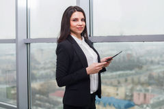 Business woman standing at window with tablet Stock Photos