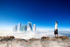 Business woman stands on the edge of mountain and looking on city. stock photos