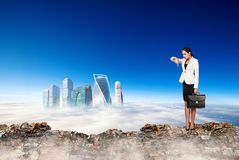 Business woman stands on the edge of mountain and looking on city. stock image