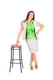 Business woman stands leaning on tall stool Royalty Free Stock Photos