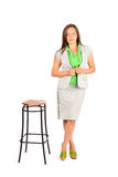 Business woman stands near tall stool Stock Image