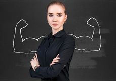 Business woman with drawn powerful hands. Business woman stands over chalkboard with drawn powerful hands Stock Photos