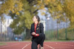 Business woman in start position ready to run and sprint on athletics racing track.  Royalty Free Stock Photography