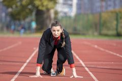 Business woman in start position ready to run and sprint on athletics racing track.  Royalty Free Stock Images
