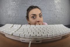Business woman sticking out from behind the keyboard stock image