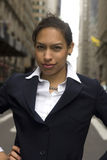 Business Woman in Street. Young African-American woman stands in street in this portrait of strength in a woman stock photo