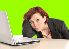 Business woman in stress at work with computer pulling her red hair isolated on green screen chroma croma. Sad business woman in stress at work with computer Stock Photos