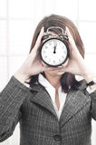 Business woman stressed by time. Business woman with a clock showing that time is passing and looking stressed Royalty Free Stock Images