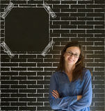 Business woman, student or teacher amrs fodled with glasses on brick wall notice board Royalty Free Stock Photo