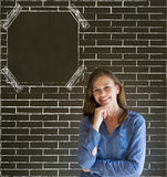 Business woman, student or teacher hand on chin on brick wall notice board Stock Photography