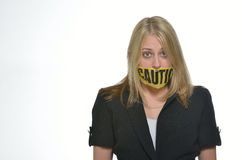 Business woman in studio - caution tape over mouth Royalty Free Stock Photography