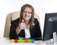 Business woman succeeds. A business woman in a business situation spells out the word succeed and gives a thumbs up sign Royalty Free Stock Photography