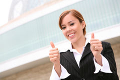 Business Woman Success. A pretty, young business woman with her thumb up showing success Stock Images