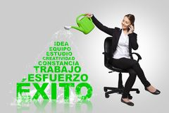 Business woman -success concept with spanish words. Portrait of a happy young business woman with success concept Stock Photography