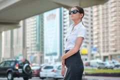 Business woman. Successful arabic businesswoman standing. In the street in formal attire. Businessman standing near skyscrapers in Dubai downtown in sunglasses Stock Images
