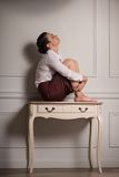Business woman suffering from depression. Full-length portrait of beautiful dark-haired fagged young woman wearing white blouse and vinous skirt sitting on the Royalty Free Stock Images