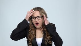 Business woman suffering from headache from fatigue against grey background, slow motion. Business woman suffering from headache from fatigue against grey stock footage