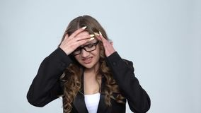 Business woman suffering from headache from fatigue against grey background, slow motion. Business woman suffering from headache from fatigue against grey stock video