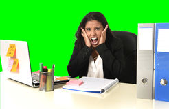 Business woman suffering stress working at office isolated green chroma key background. Young beautiful latin business woman suffering stress working at office Stock Photo