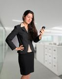 Business woman in suit on cell phone at office. Beautiful brunette woman with cell phone at work in suit Stock Images