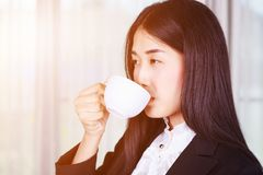 Business woman in suit drinking coffee or tea cup Stock Images