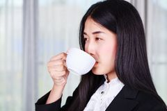 Business woman in suit drinking coffee or tea cup Stock Image