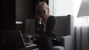 Business woman in suit and glasses typing on a laptop and thinking in the office. Business woman in suit and glasses typing on a laptop and start thinking in the stock footage
