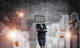 Business woman with laptop instead of head. Business woman in suit with laptop instead of head keeping arms crossed while standing against flying bulbs and Royalty Free Stock Photography