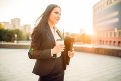 Business woman in suit with notebook and coffee. Young business woman with notebook and coffee. Modern building, financial center, cityscape. Female Royalty Free Stock Photography