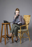 Business woman in a suit sitting in a chair with the phone talki Royalty Free Stock Photos