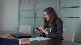 Businesswoman summing up meeting with partner and goodbye handshake. Business woman in business suit sitting at negotiating table in office. With a smile sums up stock video footage