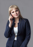 Business woman in suit talking on a cell phone. Young business woman talking on a cell phone in a suit. A woman looking down. Gray background royalty free stock photo