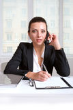 Business woman in a suit talking on a phone Royalty Free Stock Photography