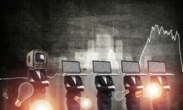 Modern technologies against old one. Business woman in suits with laptops instead of their heads keeping arms crossed while standing in a row and one at the Royalty Free Stock Photo