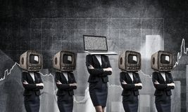 Modern technologies against old one. Business woman in suits with old TV instead of their heads keeping arms crossed while standing in a row and one at the head Royalty Free Stock Photography