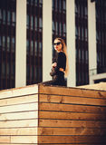 Business woman in sunglasses sitting near the office building Royalty Free Stock Photo