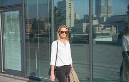 Business woman in sunglasses walking on the street holding trench coat stock photography